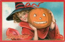 pretty witch holds jack o lantern in front of face