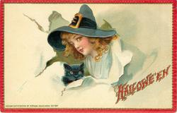 pretty young witch in large hat breaks through paper with cat