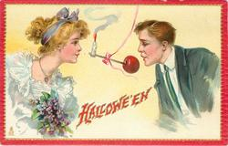 candle and apple on stick held by ribbon between man & woman