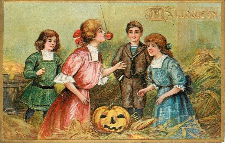woman in pink stands bobbing  for apple on string above Jack-o-Lantern on floor front, three children observe