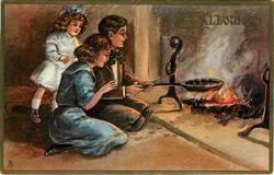 young man holds skillet over fire, woman and girl look on