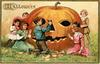 six children carving out a giant Jack-o-Lantern, boy in center cuts nose