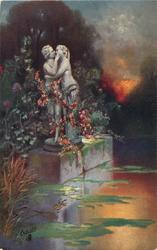 silver-lit statue in pond of couple embracing