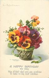 many coloured pansies in brown bowl in basket, green ribbon round