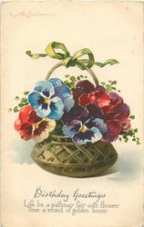 blue, red, purple, yellow coloured pansies in brown bowl in basket, green bow on top