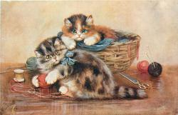 two tabby kittens, one in basket, one plays with ball of wool