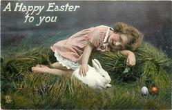 A HAPPY EASTER TO YOU  girl lies on pile of grass stroking stuffed rabbit, two Easter eggs