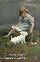 TO WISH YOU A HAPPY EASTER  girl sits on pile of grass, stuffed rabbit, three Easter eggs