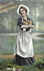 EASTER GREETINGS  woman standing holding armful of chicks, Easter eggs on ground