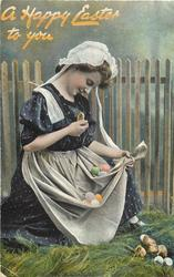 A HAPPY EASTER TO YOU  woman sitting looking down at chick she is holding, eggs in skirt & chicks around