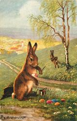 rabbit sits painting Easter eggs