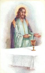 Jesus stands at table, holding wafer, wine cup on table