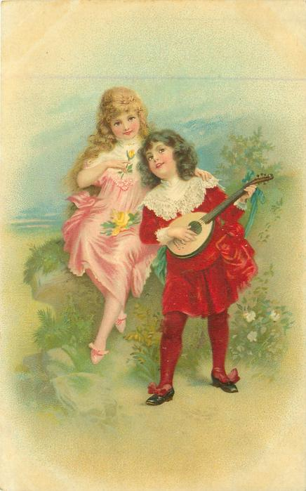 boy in red suite stands & plays mandolin to girl sitting at his side