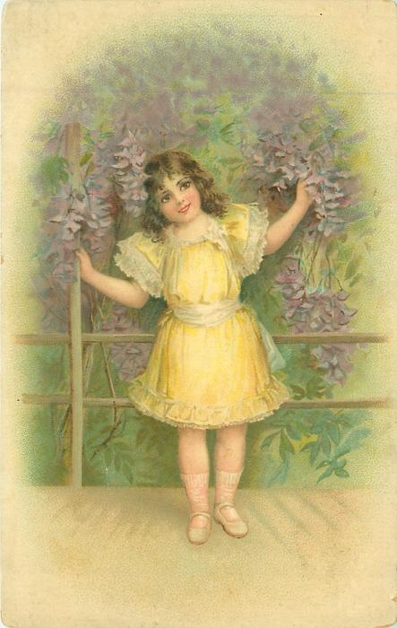 girl stands on deck with two rail fence behind, one hand holds fence post, other holds purple wisteria