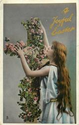 A JOYFUL EASTER  girl stands facing cross with both hands up on cross