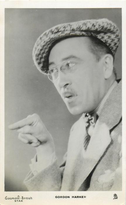 GORDON HARKER  looks & faces left, points at something, wears hat & glasses