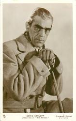 "BORIS KARLOFF APPEARING IN ""THE GHOUL""  with cane, wears coat, gloves"