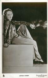 JOYCE KIRBY  sits, smoking