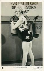 CICELY COURTNEIDGE  in bathing suit, next to fire buckets