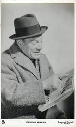 EDMUND GWENN  reads newspaper