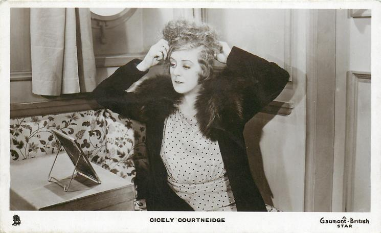 CICELY COURTNEIDGE  looking in mirror, making her hair