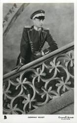 CONRAD VEIDT  in uniform, wears monocle, stands on stair