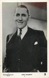 JACK HULBERT  faces & looks front, smiles, wears dark suit