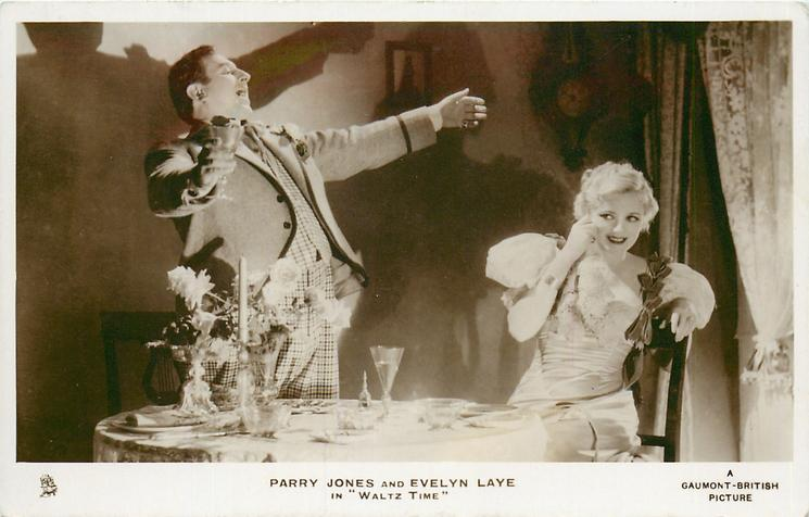 "PARRY JONES AND EVELYN LAYE IN ""WALTZ TIME""  his both hand in the air, her right hand touches her face"