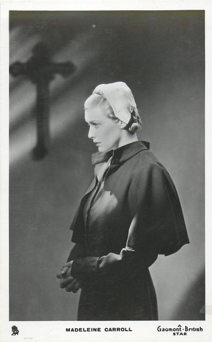 MADELEINE CARROLL  standing facing left, looking down, cross behind
