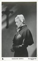 MADELEINE CARROLL  standing facing left, looking down, cross behind