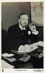 MATHESON LANG  smoking cigar, sitting at desk