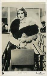 TAMARA DESNI  wearing fur, carrying case, disembarking