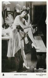JESSIE MATTHEWS  standing, with one foot up on bench, in very flimsy costume