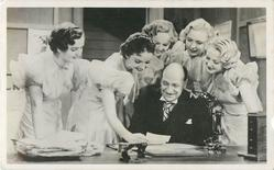 group of six, five women behind man, all look at the same paper
