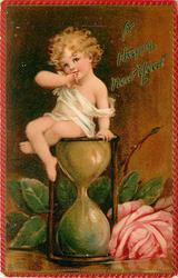 A HAPPY NEW YEAR infant sitting on top of hour glass