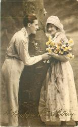 two lovers stand in front of tree trunk, she holds floral bouquet on her left arm, they look into each others eyes
