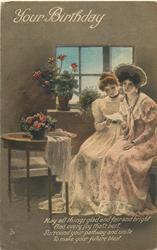 YOUR BIRTHDAY  two women sit in room with two pots of flowers, sharing a letter