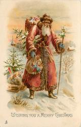 WISHING YOU A MERRY CHRISTMAS, Santa walks front/right carrying staff & toys, pulling sled