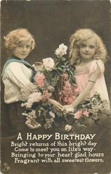 A HAPPY BIRTHDAY boy and girl hold each other's hand, face front
