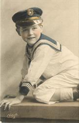 young boy in sailors uniform kneels on bench legs to right, facing left, looking front