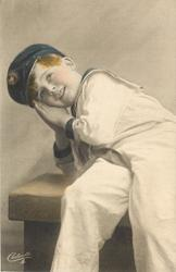 young boy in sailors uniform sits on bench leaning left with both hands together supporting head