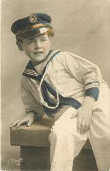 young boy in sailors uniform sits on bench leaning on his right arm, left hand on right thigh