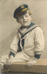young boy in sailors uniform sits on bench legs to left with both hands on front of bench