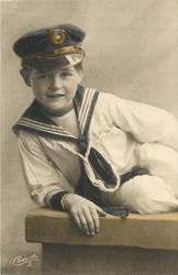 young boy in sailors uniform sits on bench legs to right, leans on his right elbow, hand on front of bench
