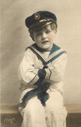 young boy in sailors uniform sits on bench legs with arms folded, looking front