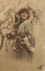 girl in kimona posed next to tree with parrot, her right elbow at birds beak, her left holds tree branches
