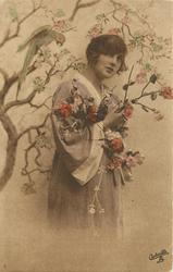 girl in kimona posed next to tree with parrot, bird on branch behind & above, her left hand hardly seen, right hand at chest level holding flowers