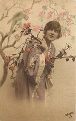 girl in kimona posed next to tree with parrot, bird near the flowers held in her right hand on right shoulder