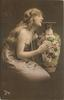 long haired model in off-shoulder dress & long string of pearls poses to left of large ornamental  vase,  left arm behind vase, right arm & hand embrace it, faces & looks right