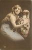 long haired model in off-shoulder dress & long string of pearls poses to left of large ornamental  vase, left hand on top of vase, right arm & hand embrace it, faces right looks  up & front